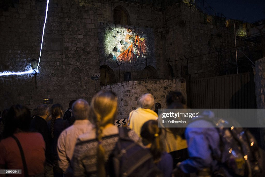 Visitors look at a light installation during the annual Jerusalem Festival of Light on June 5, 2013 in Jerusalem, Israel. During the festival light installations are projected onto the historic buildings of Jerusalem's Old City.