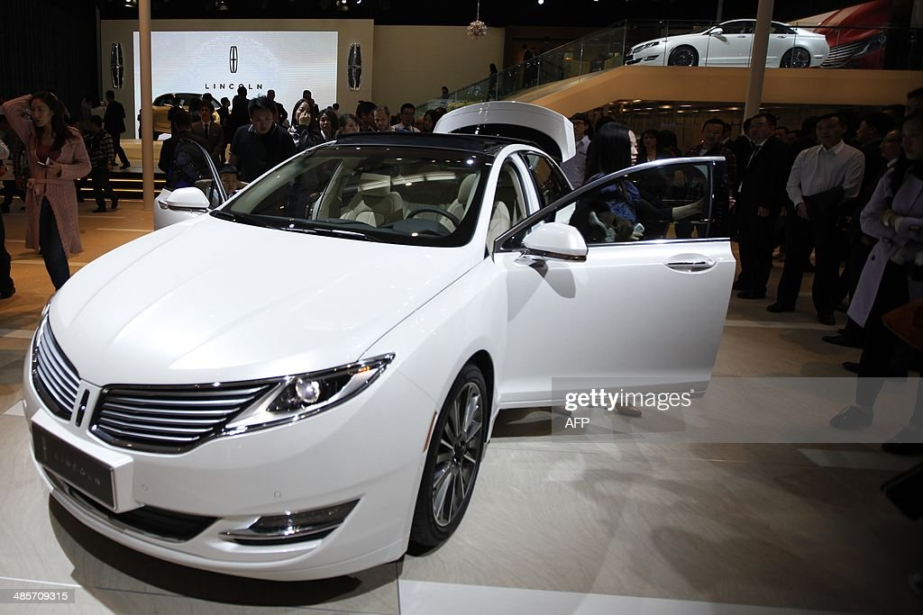 Visitors look at a Lincoln car on display at the China International Exhibition Center new venue during the 'Auto China 2014' Beijing International Automotive Exhibition in Beijing on April 20, 2014. Leading automakers are gathering in Beijing for the kickoff of China's biggest car show, but lackluster growth and environmental restrictions in the world's largest car market have thrown uncertainty into the mix. More than 1,100 vehicles are being showcased at the auto show, which opens to the public on April 21. CHINA
