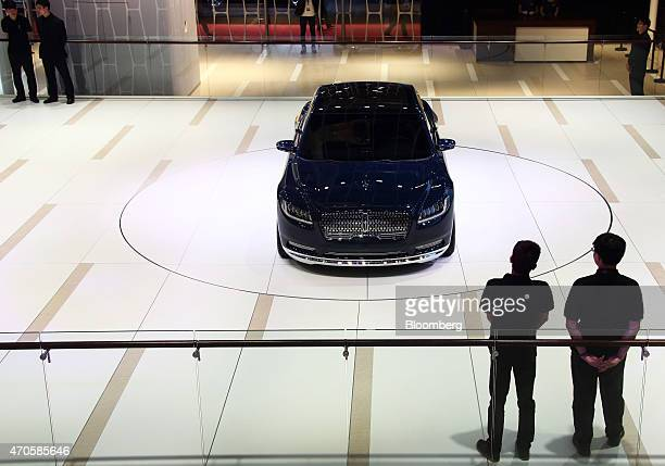 Visitors look at a Lincoln Continental luxury sedan concept vehicle produced by Ford Motor Co at the 16th Shanghai International Automobile Industry...