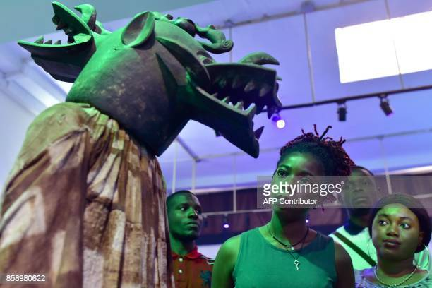 Visitors look at a mask exhibited at the Civilisation Museum of Abidjan on September 29 2017 during the first exhibition called 'Renaissance'...