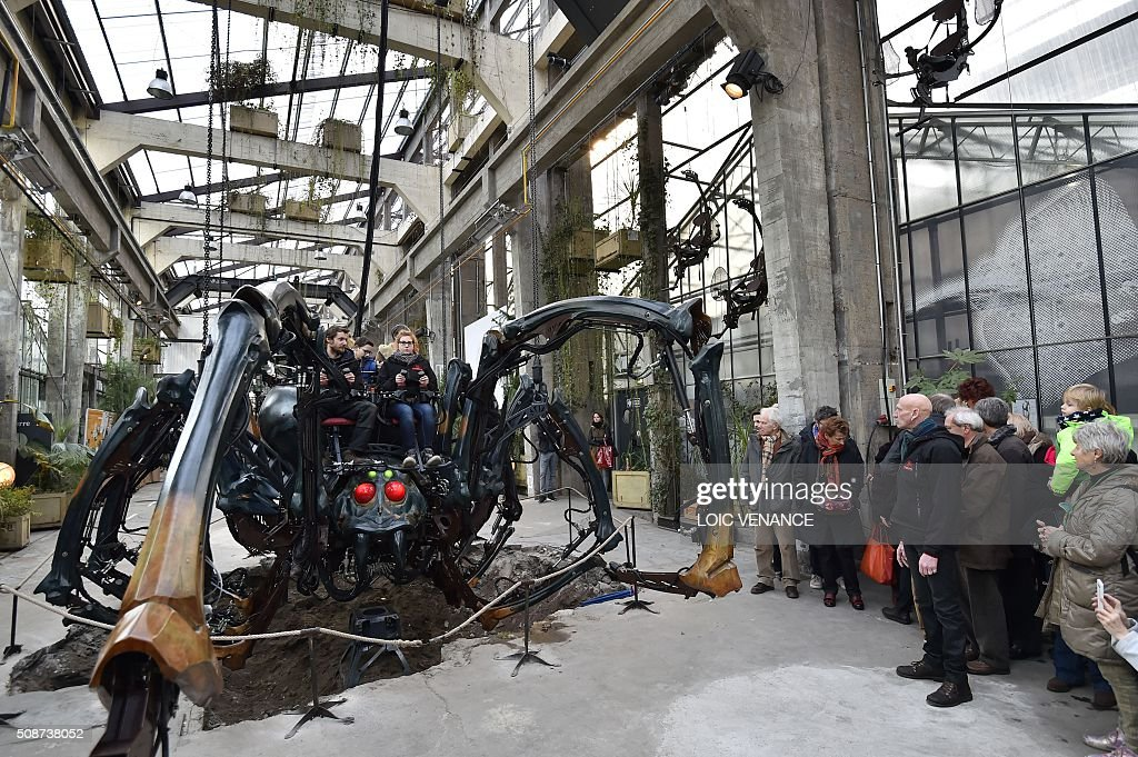 Visitors look at a mechanical spider made of wood and steel as it is presented to the public for the first time at 'Les Machines de L'Ile' ('Machines of the Isle of Nantes') in Nantes, western France, on February 6, 2016. / AFP / LOIC VENANCE