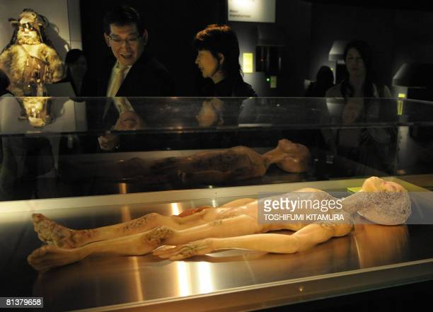 Visitors look at a model depicting the 1947 Alien Autopsy in Roswell New Mexico during the 'The Science of Aliens' exhibition at the Miraikan the...