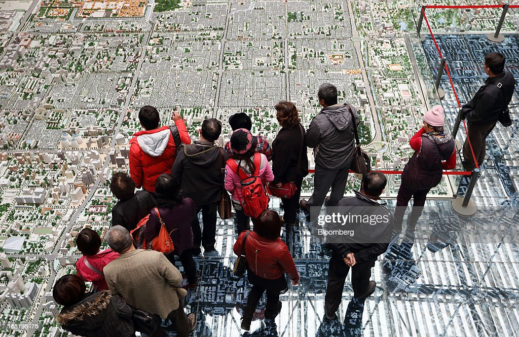 Visitors look at a model of the city of Beijing at the Beijing Planning Exhibition Hall in Beijing, China, on Wednesday, March 6, 2013. China maintained its economic-growth target at 7.5 percent for 2013 while setting a lower inflation goal of 3.5 percent, setting up a challenge for new leaders to keep prices in check without harming expansion. Photographer: Tomohiro Ohsumi/Bloomberg via Getty Images