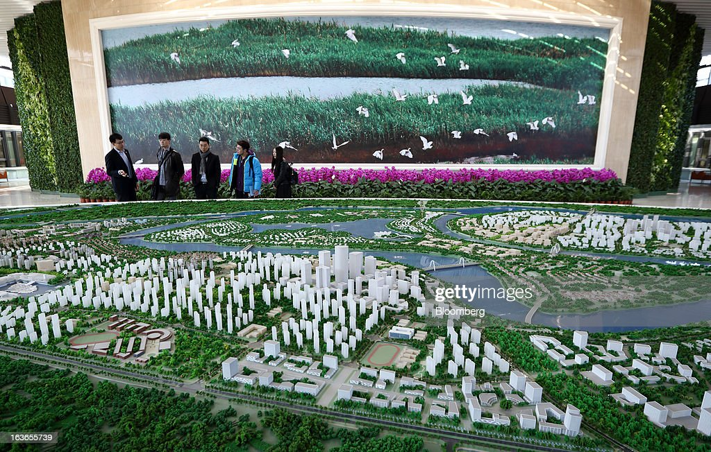 Visitors look at a model of the Sino-Singapore Tianjin Eco-city in a showroom in Tianjin, China, on Wednesday, March 13, 2013. China's money-market rate rose to a one-week high after central bank Governor Zhou Xiaochuan said yesterday the nation should be on 'high alert' over inflation. Photographer: Tomohiro Ohsumi/Bloomberg via Getty Images