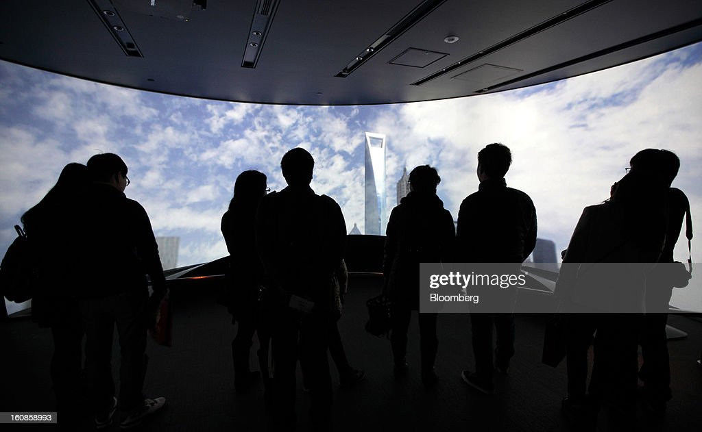 Visitors look at a monitor displaying an image of the Shanghai World Financial Center in the Pudong area of Shanghai, China, on Saturday, Feb. 2, 2013. China's economic growth accelerated for the first time in two years as government efforts to revive demand drove a rebound in industrial output, retail sales and the housing market. Photographer: Tomohiro Ohsumi/Bloomberg via Getty Images