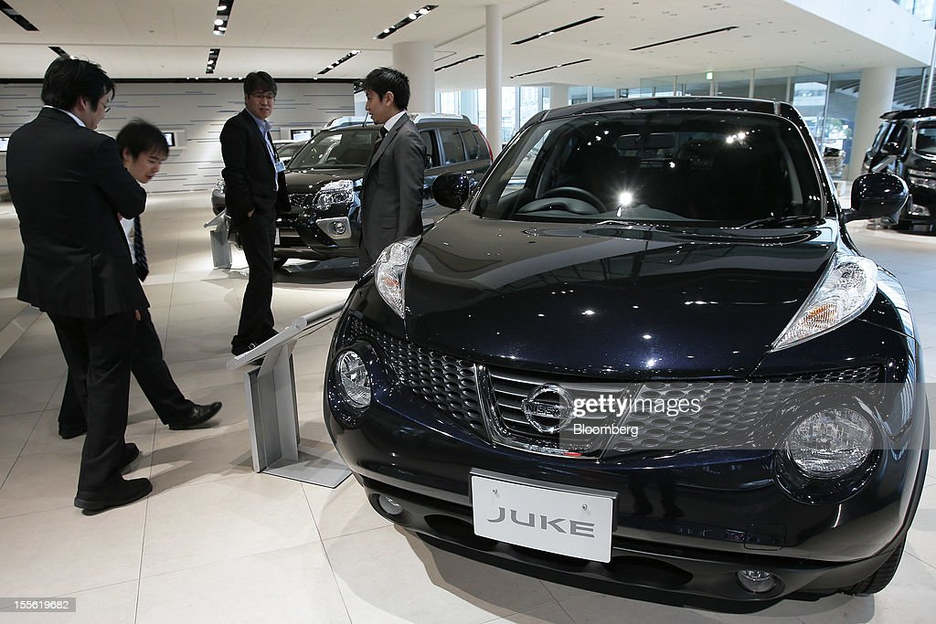 Visitors look at a Nissan Motor Co. Juke vehicle displayed at the company's headquarters in Yokohama City, Kanagawa Prefecture, Japan, on Tuesday, Nov. 6, 2012. Nissan, the top Japanese seller of vehicles in China, cut its full-year net income forecast 20 percent after consumer backlash stemming from a territorial dispute sent sales lower in its largest market. Photographer: Kiyoshi Ota/Bloomberg via Getty Images