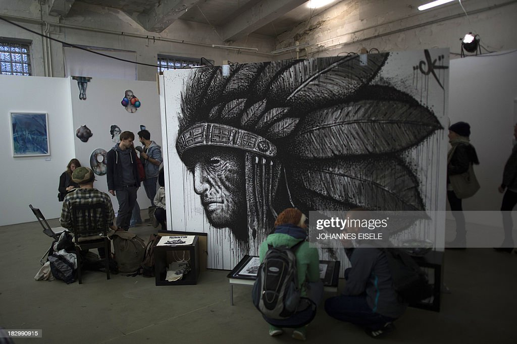 CAPTION Visitors look at a painting by German artist Christopher Kieling at the Stroke Art Fair in Berlin on October 3, 2013. AFP PHOTO / JOHANNES EISELE