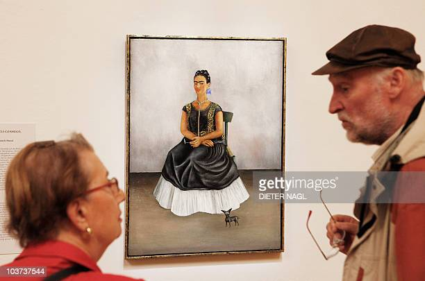 Visitors look at a painting by Mexican artist Frida Kahlo titled 'selfportrait with Itzcuintlidog' during the opening of a show of her works on...