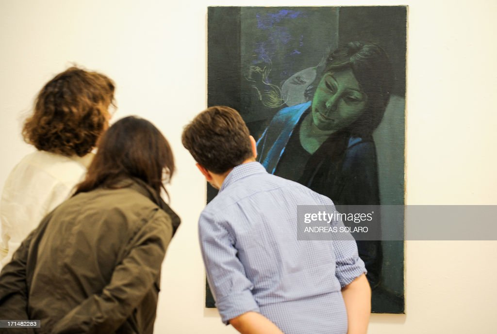 Visitors look at a painting entitled 'Sirens' by' Romanian artist Victor Man on June 25, 2013 during an exhibition at the Villa Medici, the headquarters of the French Academy in Rome.