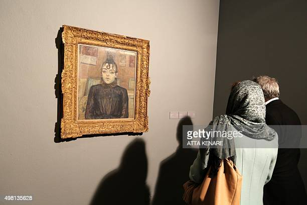 Visitors look at a painting titled 'Girl with lovelock' by French artist Henri de Toulouse Lautrec during the opening ceremony of an exhibition of...