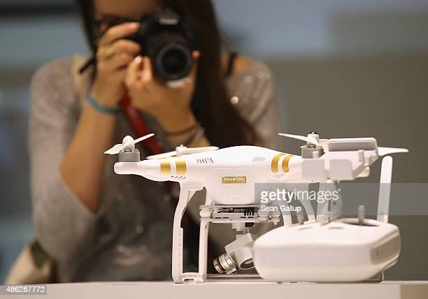 Visitors look at a Phantom 3 Professional quadcopter drone at the DJI stand during a press day at the 2015 IFA consumer electronics and appliances...