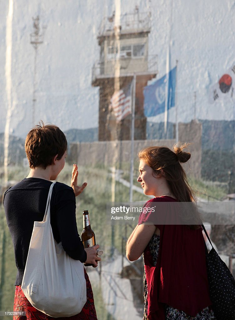 Visitors look at a photo of the North and South Korean border's Demilitarized Zone (DMZ) as part of the 'Wall on Wall' exhibition at the East Side Gallery section of the former Berlin Wall on July 10, 2013 in Berlin, Germany. A series of photos shot since 2006 by photographer Kai Wiedenhoefer hanging on the Western, river Spree side of the Wall features large pictures of separation barriers in Baghdad, Korea, Cyprus, Mexico, Morocco, Israel, Belfast, and in the former East Germany itself. The opposite side of the stretch of the original Wall is known as East Side Gallery, a memorial to peace and freedom covered in murals questioning the legacy of the original Wall, and the subject of several demonstrations earlier in March this year when sections of it were threatened with removal to make way for a construction site for luxury apartment buildings, discussion of which is still ongoing with a decision expected to be reached in early August.