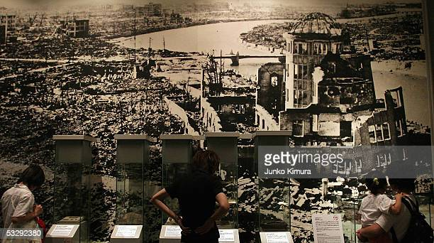 Visitors look at a picture showing the aftermath of the atomic bomb attack at the museum ahead of the 60th anniversary of the dropping of the first...