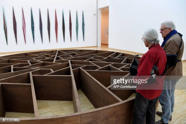 Visitors look at a piece of art called 'Par une foret obscure' by French artist Daniel Dezeuze displayed at the Musee de Grenoble in Grenoble on...
