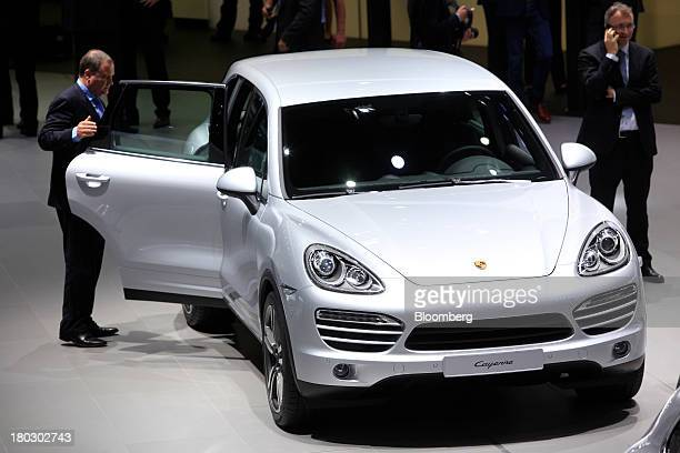 Visitors look at a Porsche Cayenne automobile produced by Porsche SE at the 65th Frankfurt International Motor Show in Frankfurt Germany on Wednesday...