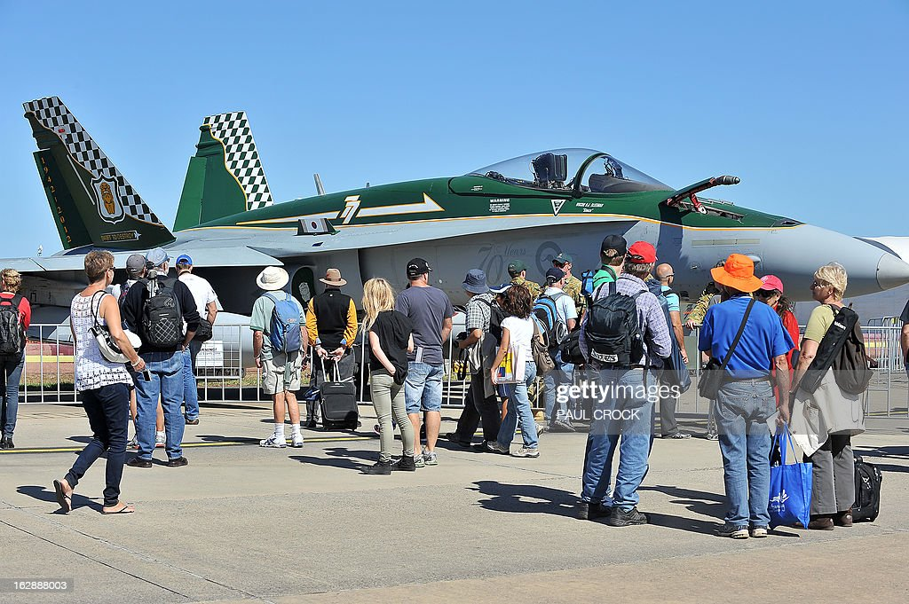 Visitors look at a Royal Australian Air Force F-18 Hornet during the Australian International Airshow in Melbourne on March 1, 2013. 180,000 patrons are expected through the gates over the duration of the event staged at the Avalon Airfield some 80kms south-west of Melbourne. AFP PHOTO / Paul CROCK
