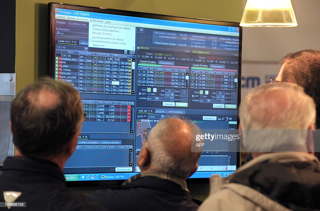 Visitors look at a screen at the French online bank Fortuneo's stand during the Actionaria shareholders event in Paris on November 23, 2012. AFP PHOTO / ERIC PIERMONT