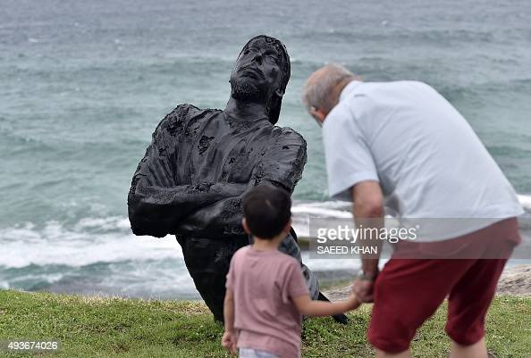 Visitors look at a sculpture by artist Louis Pratt at the 'Sculpture by the Sea' exhibition which runs along the Bondi to Tamarama coastal walk in...