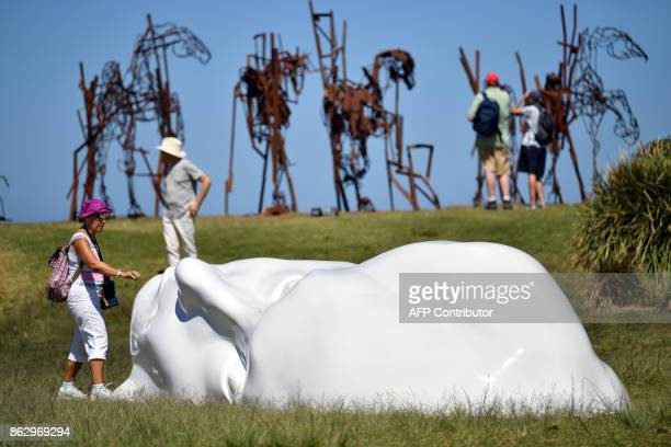 Visitors look at a sculpture by artist Sonia Payes at the 'Sculpture by the Sea' exhibition near Bondi beach in Sydney on October 19 2017 The...