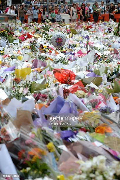 Visitors look at a sea of flowers at a makeshift memorial near the scene of a fatal siege in the heart of Sydney's financial district on December 18...