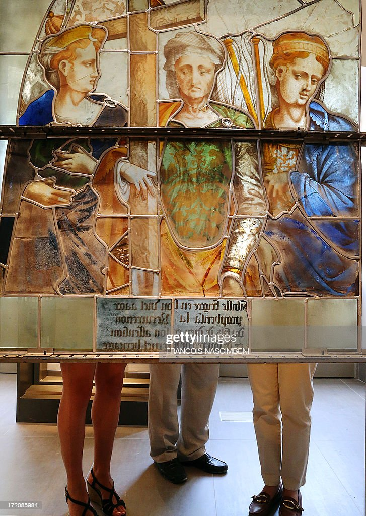 Visitors look at a stained-glass window on July 1, 2013 during the permanent exhibition at 'La Cité du Vitrail' (stained-glass center) at the Hotel-Dieu-le Comte in Troyes, in the French eastern department of Aube, highlighting a medieval heritage which gathers one of France's most valuable collections of ancient stained-glass windows, mainly dated from the fifteenth and sixteenth centuries.