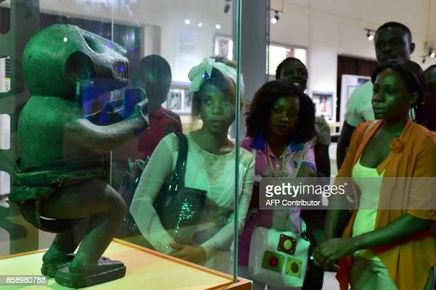 Visitors look at a statue exhibited at the Civilisation Museum of Abidjan on September 29 2017 during the first exhibition called 'Renaissance'...