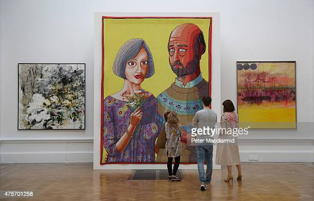 Visitors look at a tapestry by artist Grayson Perry called 'Julie and Rob' in the Summer Exhibition at The Royal Academy on June 3 2015 in London...