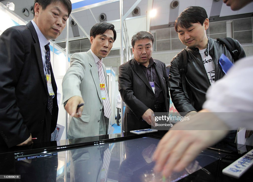 Visitors look at a touch panel displayed at the Finetech Japan exhibition in Tokyo, Japan, on Wednesday, April 11, 2012. Finetech Japan, the world's largest flat panel display exhibition, will be held through April 13. Photographer: Tomohiro Ohsumi/Bloomberg via Getty Images