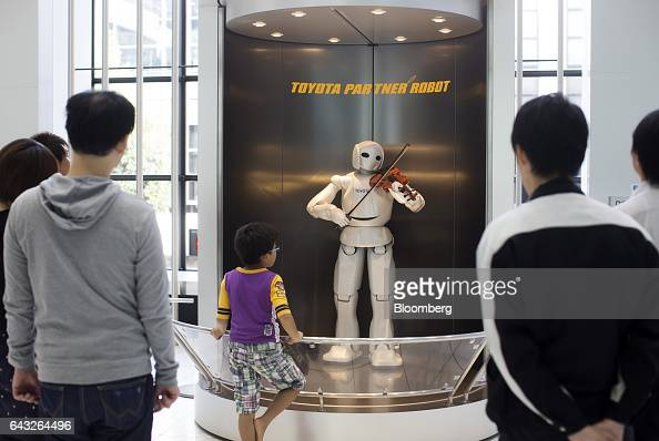 Visitors look at a Toyota Motor Corp Partner Robot playing a violin in the showroom at the company's headquarters in Toyota City Aichi Japan on...