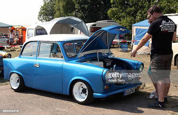 Visitors look at a Trabant automobile during a Trabant enthusiasts' weekend on August 8 2015 near Nossen Germany The Trabant also called the Trabi is...