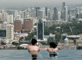 Visitors look at a view of the city skyline from the rooftop pool of the Marina Bay Sands resort hotel in Singapore on May 20 2014 Singapore's...