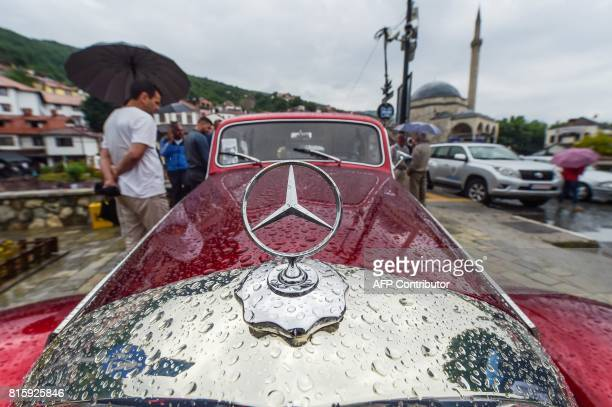 Visitors look at a vintage Mercedes displayed during the 12th Old Timer Fest on July 17 2017 in the historic city of Prizren in southern Kosovo / AFP...