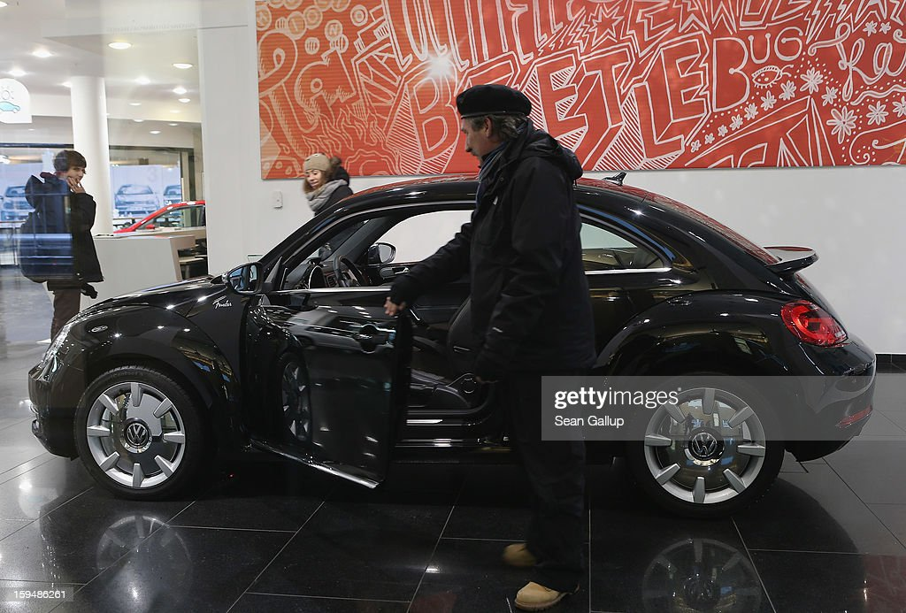 Visitors look at a VW Beetle at a Volkswagen Group showroom on January 14, 2013 in Berlin, Germany. Volkswagen Group, which includes the VW, Audi, Porsche, Skoda, SEAT, Bentley and Bugatti brands, delivered a record 9.07 million cars to customers in 2012. Rising sales in the Americas and Asia helped to offset a drop in sales in western Europe.