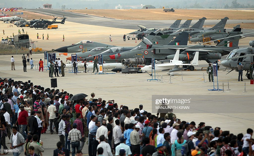 Visitors look at aircraft parked at the static display area on the third day of Aero India 2013 at Yelahanka Air Force station in Bangalore on February 8, 2013. India, the world's leading importer of weaponry, opened one of Asia's biggest aviation trade shows February 6 with Western suppliers eyeing lucrative deals and a Chinese delegation attending for the first time. AFP/Manjunath KIRAN