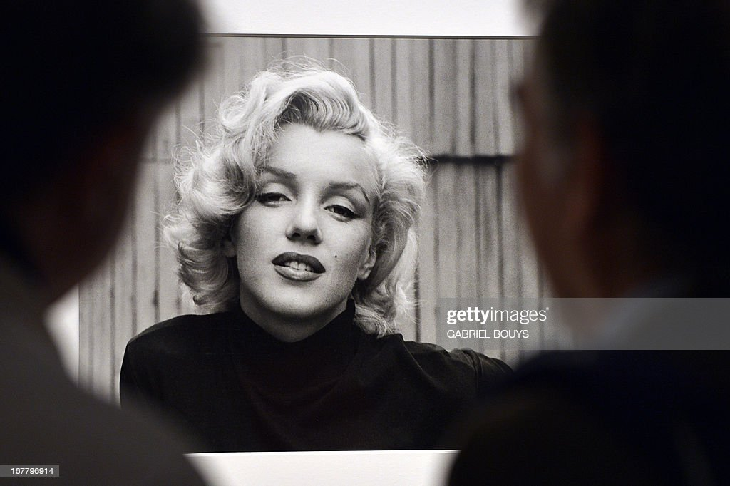 """Visitors look at Alfred Eisenstaedt's """"Marilyn Monroe, Hollywood, USA, 1953"""" during the 'Life. I grandi fotografi' (Life. The great photographers) exhibition at the auditorium on April 30, 2013 in Rome. The exhibition showing some 150 pictures taken from 1936 when the US magazine Life magazine premiered will be open from May, 1 to August 4, 2013. AFP PHOTO / GABRIEL BOUYS AFP PHOTO / GABRIEL BOUYS RESTRICTED TO EDITORIAL USE, MANDATORY CREDIT OF THE ARTIST, TO ILLUSTRATE THE EVENT AS SPECIFIED IN THE CAPTION"""