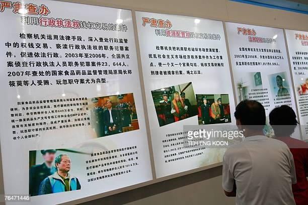 Visitors look at an anti corruption billboard featuring the alleged corruption communist party members displayed at an exhibition in Beijing 02...