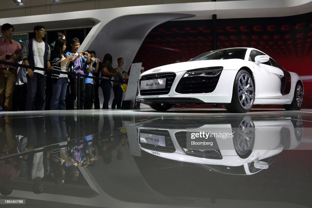 Visitors look at an Audi R8 vehicle at the FAW Audi booth, the joint venture between Audi AG, Volkswagen AG, and FAW Group Corp., at the Wuhan Motor Show 2013 in Wuhan, China, on Saturday, Oct. 19, 2013. The show will be held through Oct. 23. Photographer: Tomohiro Ohsumi/Bloomberg via Getty Images