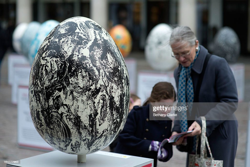 Visitors look at an egg entitled 'How Mind Came Into The World' by Whitney McVeigh one of the giant fibreglass easter eggs on display in Covent Garden before the Big Egg Hunt on March 22, 2013 in London, England. Each egg is two and a half feet tall and designed by a leading artist.