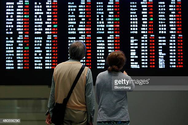 Visitors look at an electric stock board at the Tokyo Stock Exchange operated by Japan Exchange Group Inc in Tokyo Japan on Monday July 13 2015...