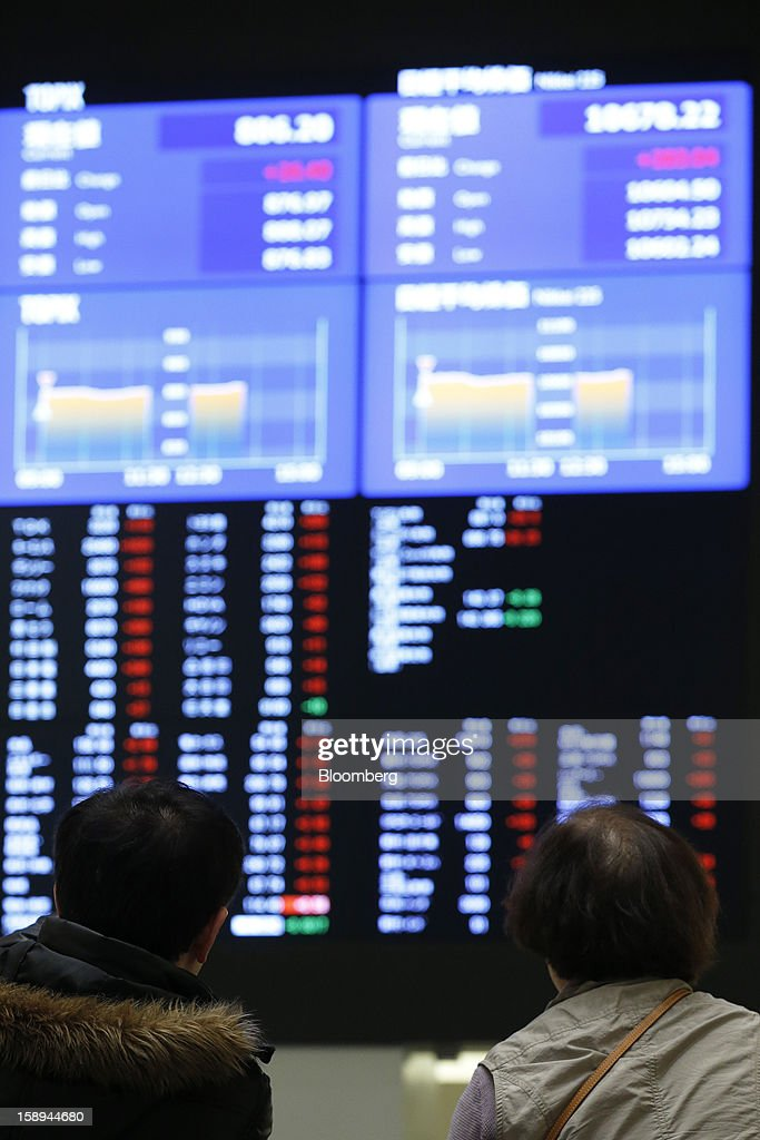 Visitors look at an electronic board displaying the Nikkei 225 Stock Average figure, top right, and share prices at Japan Exchange Group Inc.'s Tokyo Stock Exchange (TSE) on the first trading day of the year in Tokyo, Japan, on Friday, Jan. 4, 2013. Japan Exchange, created by the merger of Japan's two biggest bourses, fell in its trading debut on the Tokyo Stock Exchange. Photographer: Kiyoshi Ota/Bloomberg via Getty Images