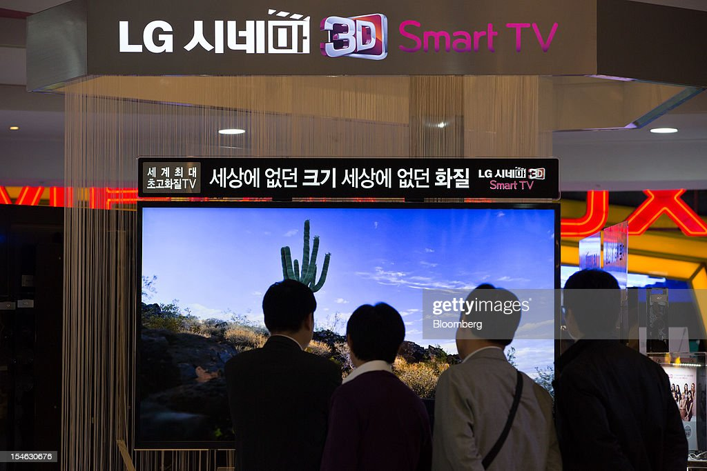 Visitors look at an LG Electronics Inc. Cinema 3D television at the company's showroom in the COEX mall in Seoul, South Korea, on Tuesday, Oct. 23, 2012. LG is scheduled to release third-quarter earnings today. Photographer: SeongJoon Cho/Bloomberg via Getty Images