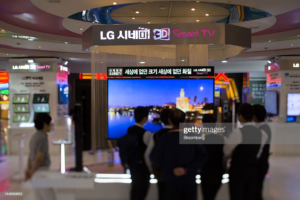Visitors look at an LG Electronics Inc. Cinema 3D television in this photograph taken with a tilt-shift lens at the company's showroom in the COEX mall in Seoul, South Korea, on Tuesday, Oct. 23, 2012. LG is scheduled to release third-quarter earnings today. Photographer: SeongJoon Cho/Bloomberg via Getty Images