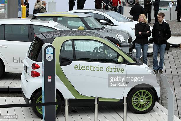 Visitors look at an outdoor presentation of electric cars by auto manufacturers Smart Volkswagen Mini and Opel as part of the German government's...
