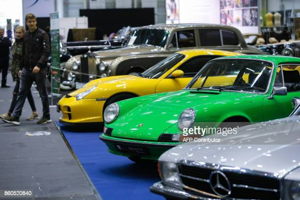 Visitors look at antique MercedesBenz und Porsche luxury cars on October 12 2017 in Hamburg on the eve of the opening of the first edition of the...