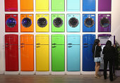 Visitors look at coloured refrigerators and other appliances on display at the Vestel stand at the 2014 IFA home electronics and appliances trade...