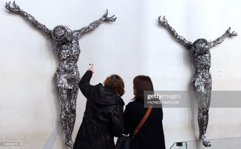 Visitors look at contemporary sculptures untitled 'Decor' by Algerian artist Adel Abdessemed on April 24, 2012 at the chapel of the Unterlinden museum in the northeastern French city of Colmar, exhibited besides the 'Isenheim Altarpiece' (aka 'retable d'Issenheim' in French) by German Renaissance painter Matthias Grunewald, as part of the 500-year anniversary of this famed Renaissance religious work. Abdessemed borrowed the image of Christ crucified from Mattias Grünewald to create four crucified Christ, laced with industrial grade razor wire. His work will be shown for the first time in Europe from April 27 to September 16, 2012 in Colmar.