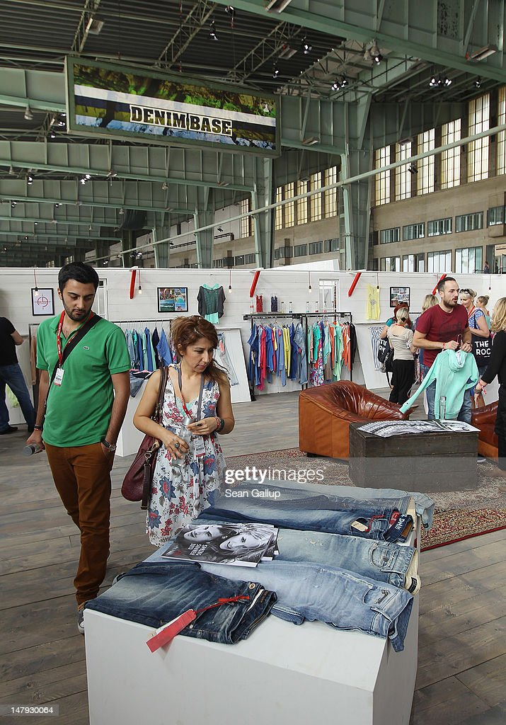 Visitors look at denim at the Fuga stand at the 2012 Bread & Butter fashion trade fair at former Tempelhof Airport on July 6, 2012 in Berlin, Germany. Bread & Butter is the world's largest trade fair for street fashion.