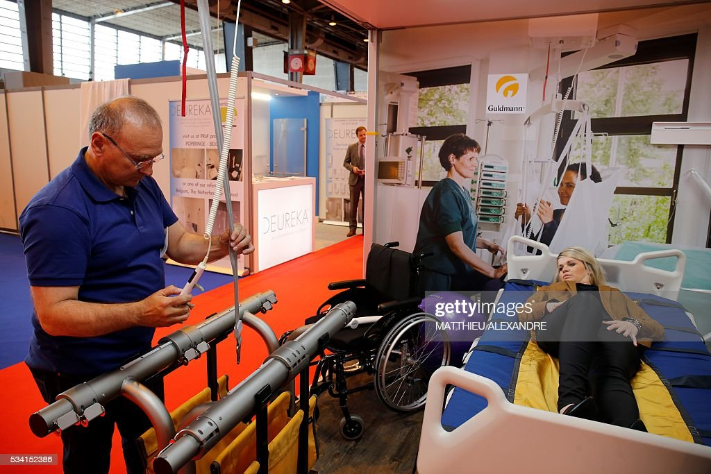Visitors look at equipment on display at a stand during Paris Healthcare week on May 25, 2016 in the French capital. / AFP / MATTHIEU