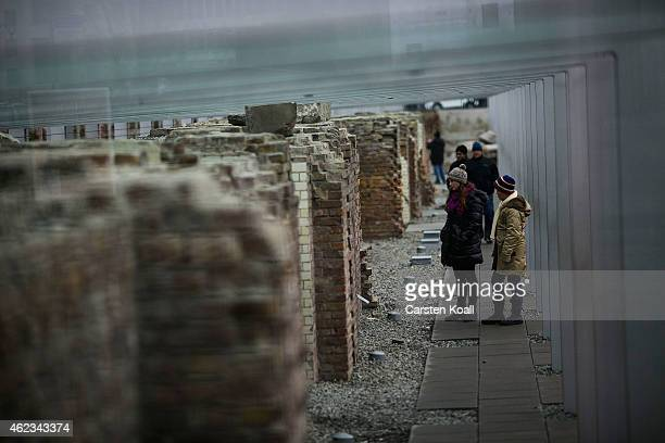 Visitors look at exhibits at the Topography of Terror documentation center and museum on January 27 2015 in Berlin Germany Thousands of people will...