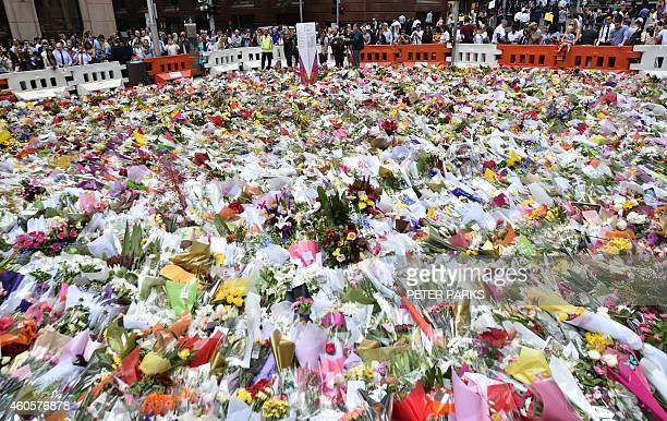 Visitors look at flowers at a makeshift memorial near the scene of a fatal siege in the heart of Sydney's financial district on December 17 2014...